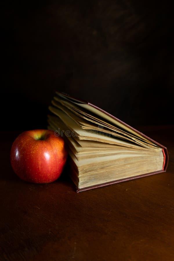 het oude dilapidated boek in een helft-draai ligt op een donkere houten achtergrond met rood Apple stock afbeeldingen