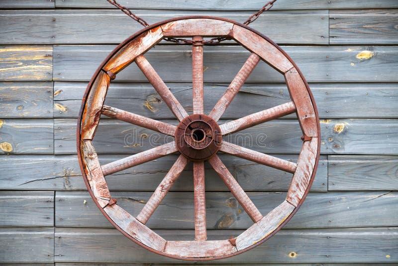 Het oude gebruikte houten wiel hangen op landelijke muur stock foto