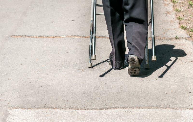 Het oude gehandicapte die vrouw lopen alleen en gedeprimeerd op de straat in de stad door regelbaar leurderstok of riet wordt geh royalty-vrije stock foto's