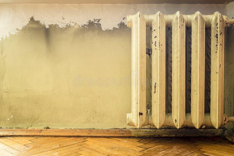 Het oude gietijzerradiator hangen op de muur stock foto's