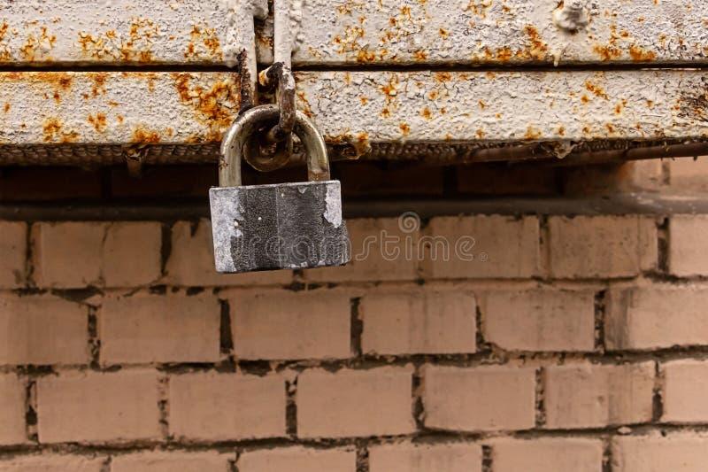 Het oude grijze slot van de hangslotveiligheid op een achtergrond van de metaal roestige doos en een bakstenen muur grunge achter royalty-vrije stock afbeelding
