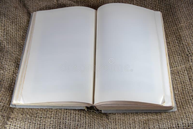 Het oude hardcoverboek met dogearred blanco pagina's die op jute liggen - ruimte voor exemplaar royalty-vrije stock afbeelding