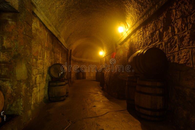 Het oude houten vat onder elektrische lamp in donkere wijnmakerij, sluit omhoog p stock foto