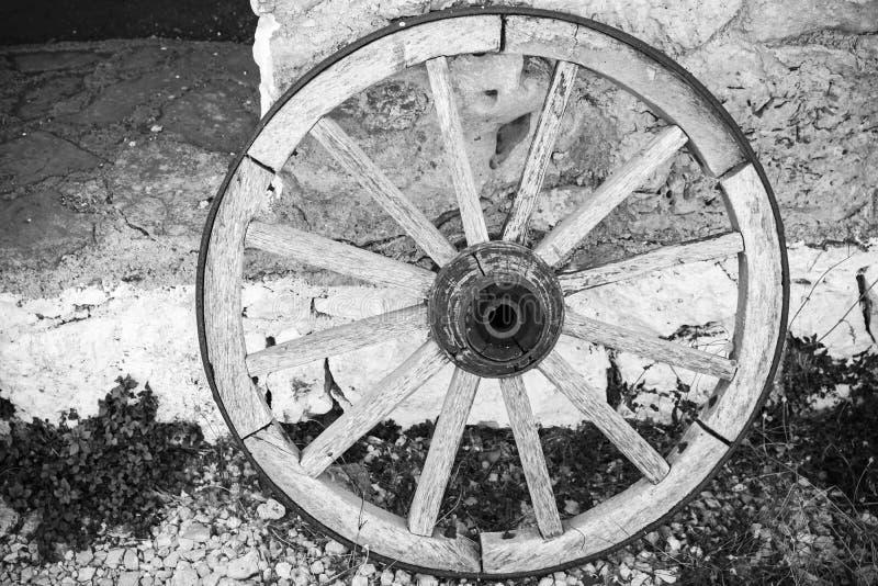 Het oude houten wiel bevindt zich dichtbij landelijke muur stock fotografie