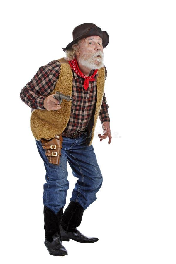 Het oude kanon van de cowboyholding kijkt vreselijk stock fotografie