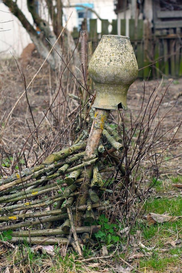 Het oude klei gebroken waterkruik hangen op een rieten omheining stock afbeelding