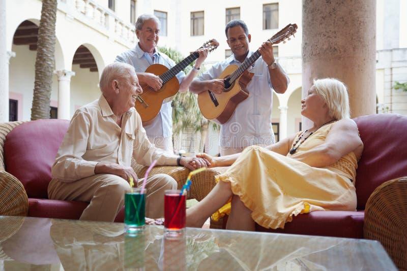 Het oude man en vrouwen drinken in hotelstaaf stock foto