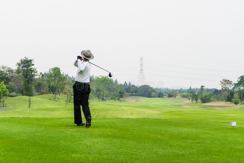Het oude mens golfing alleen op een groene golfcursus royalty-vrije stock foto's