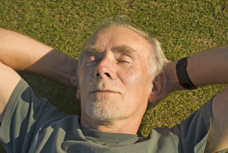 Het oude mens ontspannen in de zon op gras stock fotografie