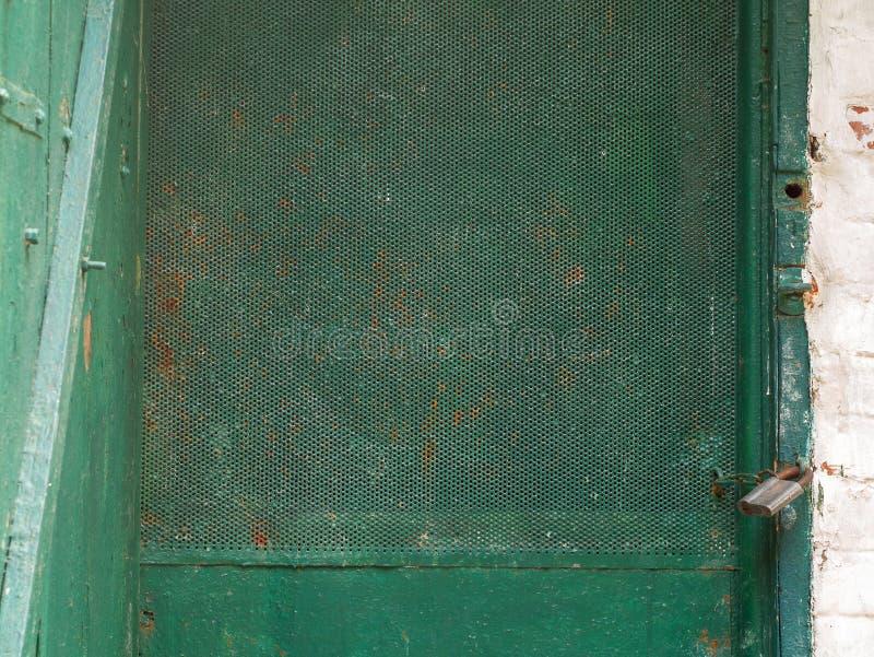 Het oude metaal en de houten deur met een roestig slot in een voorlopige kelder groeven in de grond stock afbeelding