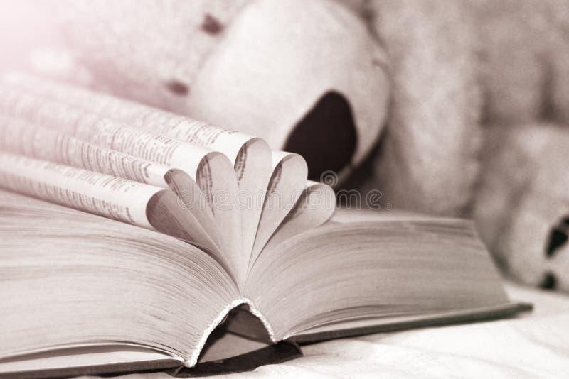 Het oude open boek met gevouwen pagina's en draagt stuk speelgoed royalty-vrije stock foto