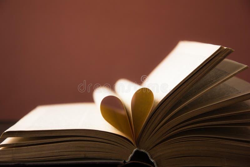 Het oude open boek met harde kaftboek, pagina verfraait in een hartvorm voor liefde in Valentine ` s liefde met open boekhart royalty-vrije stock foto's