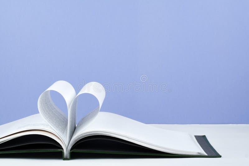 Het oude open boek met harde kaftboek, pagina verfraait in een hartvorm voor liefde in Valentine ` s liefde met open boekhart stock foto's
