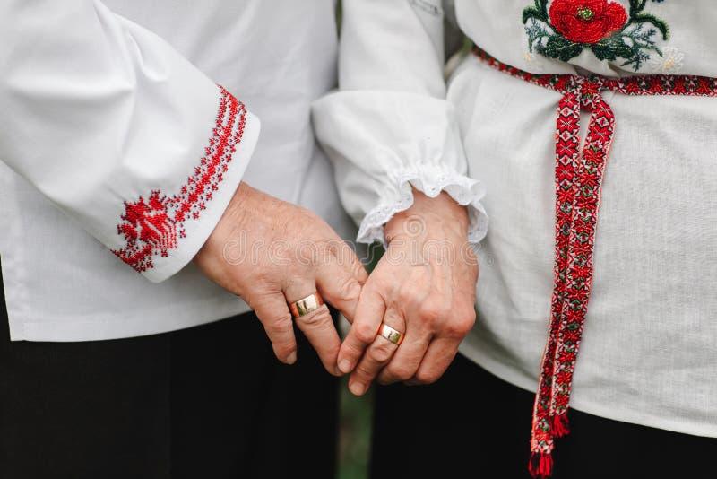 Het oude paar houdt handen Sluit omhoog van hogere man en vrouwenholdingshanden en in openlucht het lopen stock afbeelding