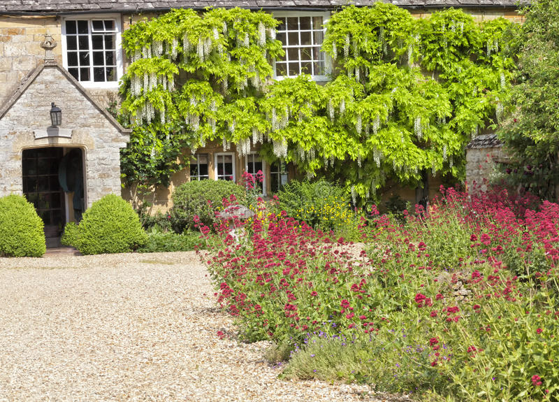 Het oude plattelandshuisje van steencotswold met de tuin van de binnenplaatsbloem royalty-vrije stock fotografie