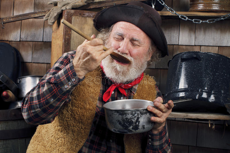 Het oude proevende voedsel van de cowboykok van openluchtkeuken royalty-vrije stock afbeelding