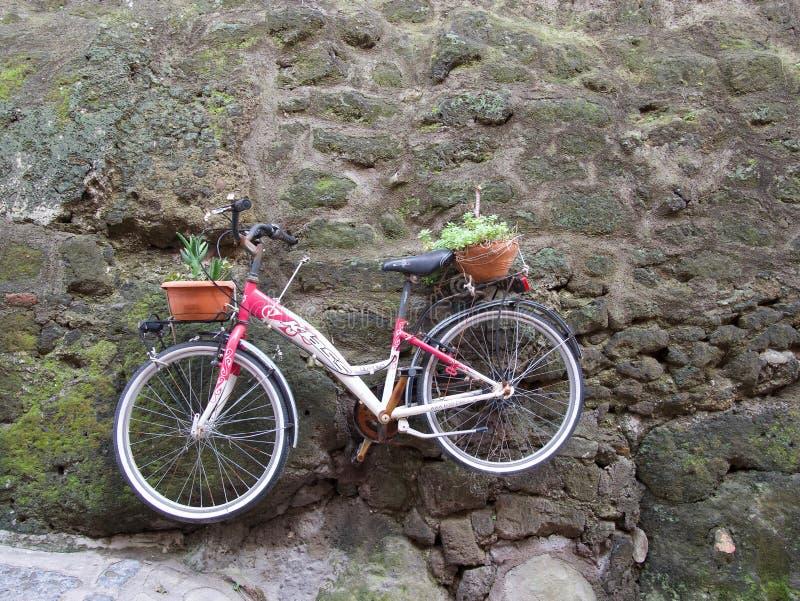 Het oude rode fiets hangen op een steenmuur stock foto