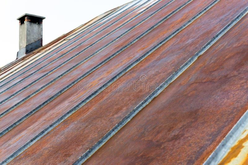 Het oude roestige dak van het ijzermetaal met schoorsteen stock afbeelding