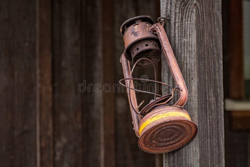 Het oude, roestige lamp hangen op post stock foto