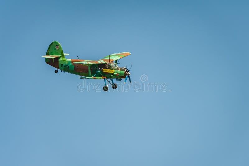 Het oude tweedekkervliegtuig vliegt en toont prestaties bij airshow in de duidelijke blauwe hemel royalty-vrije stock afbeelding