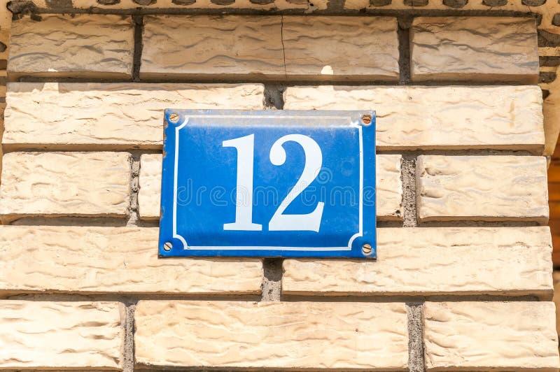 Het oude uitstekende blauwe metaal nummer 12 twaalf van het huisadres op de baksteenvoorgevel van woningbouw buitenmuur aan de st stock foto