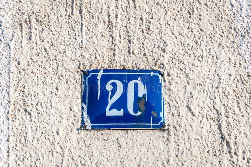 Het oude uitstekende blauwe metaal nummer 20 twintig van het huisadres op de pleistervoorgevel van verlaten huis buitenmuur aan d royalty-vrije stock foto