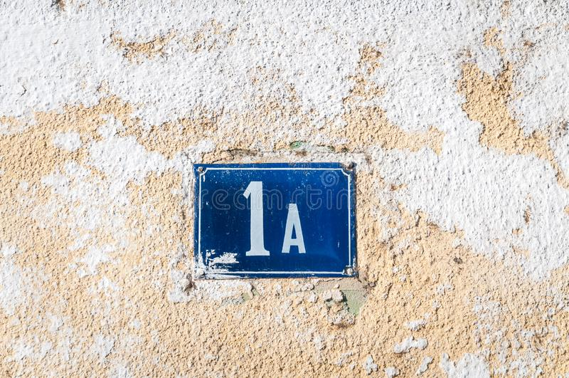 Het oude uitstekende blauwe metaal nummer 1 A van het huisadres op de pleistervoorgevel van verlaten huis buitenmuur aan de straa stock afbeelding