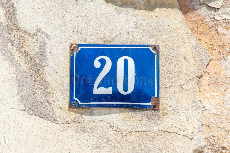 Het oude uitstekende metaal nummer 20 twintig van het huisadres op de pleistervoorgevel van verlaten huis buitenmuur aan de straa stock fotografie