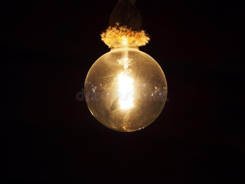 Het oude uitstekende stoffige de gloeilamp van Edison hangen op een kabelinrichting die tegen een zwarte achtergrond gloeien stock foto