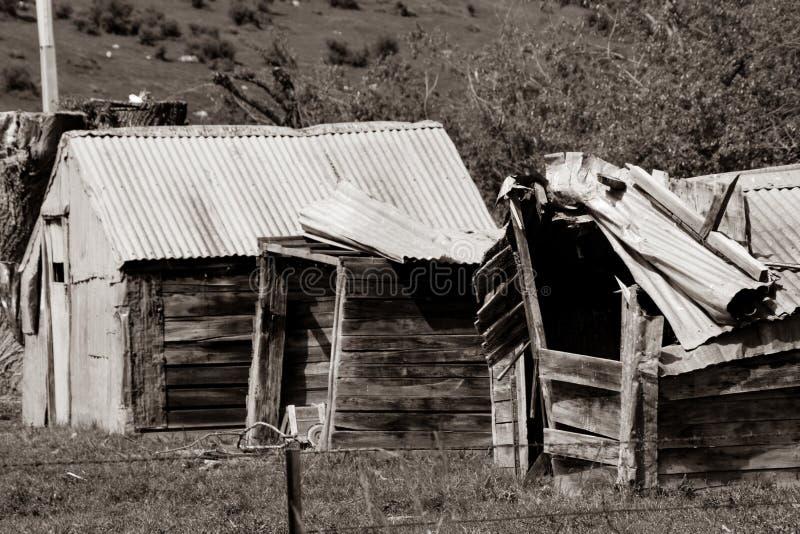 Het oude vallen onderaan rustieke landbouwbedrijfloodsen in sepia gestemd beeld stock fotografie