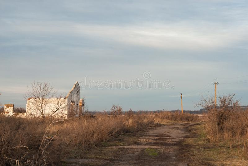 Het oude verlaten uitgestorven die dorp, aard wint het grondgebied terug door de mens, overwoekerd onkruid op plaats van binnenpl stock foto