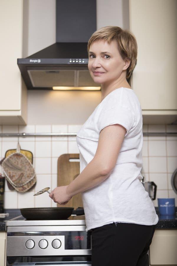 Het oude vrouw koken in haar huis bij keuken Toevallige uitrusting Portrai royalty-vrije stock fotografie