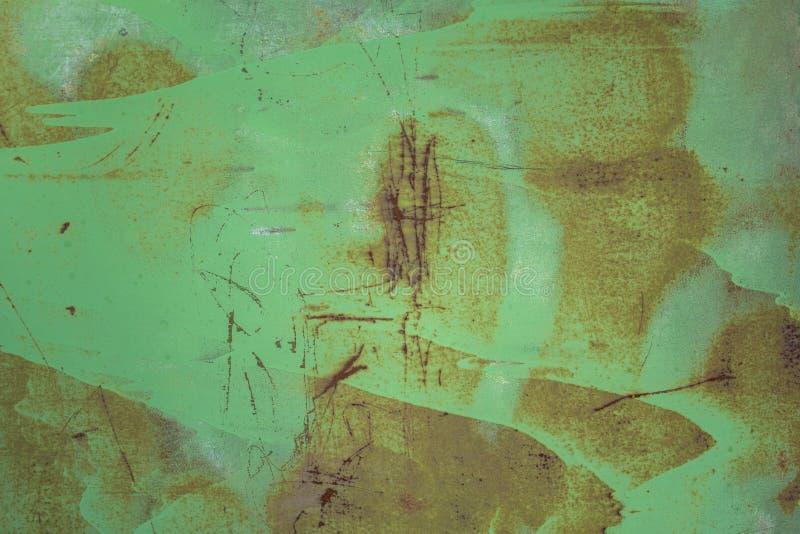 Het oude vuile groene schild van de metaalmuur met vlekken van verf, diepe krassen en punten van de bruine textuur van de roest r stock fotografie