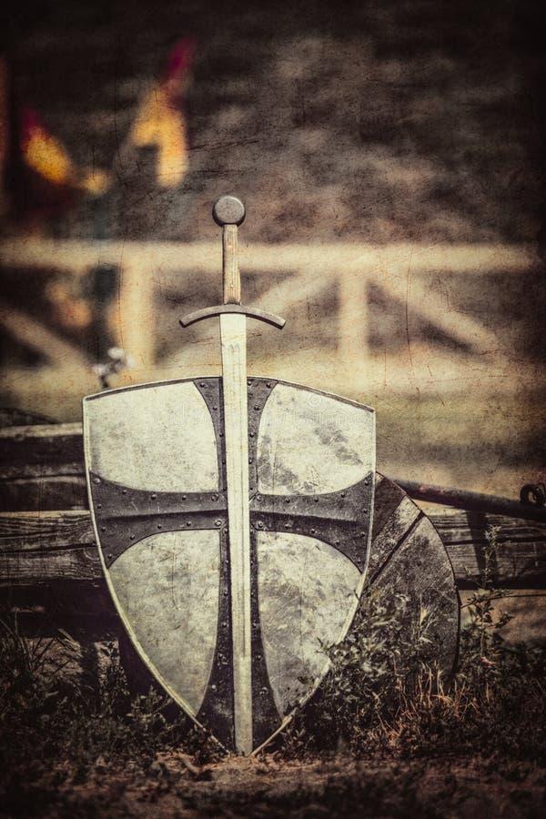 Het oude zwaard en het schild op de kasteelachtergrond royalty-vrije stock afbeeldingen