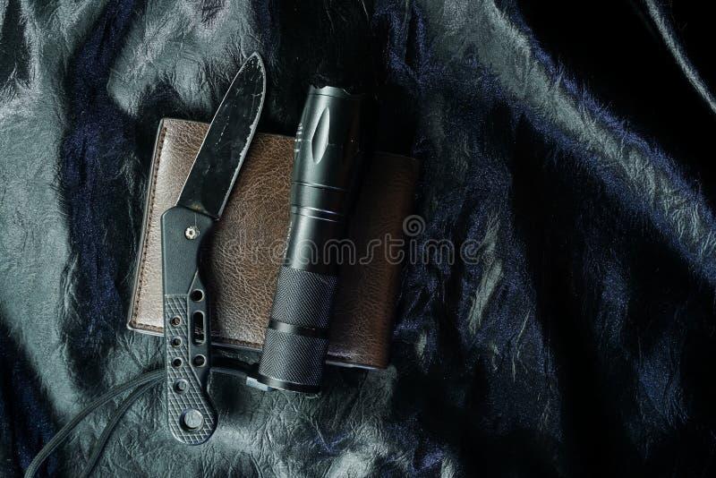 Het oude zwarte vouwende mes op de zwarte stof is glanzend stock afbeelding