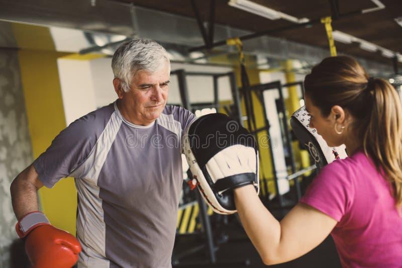 Het oudere mens in dozen doen in gymnastiek stock afbeeldingen