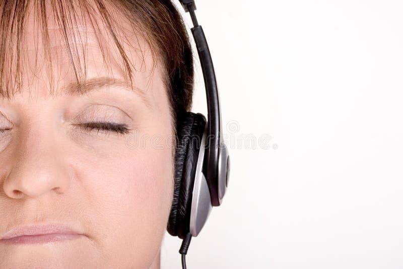 Het oudere vrouwelijke luisteren aan muziek op hoofdtelefoons stock fotografie
