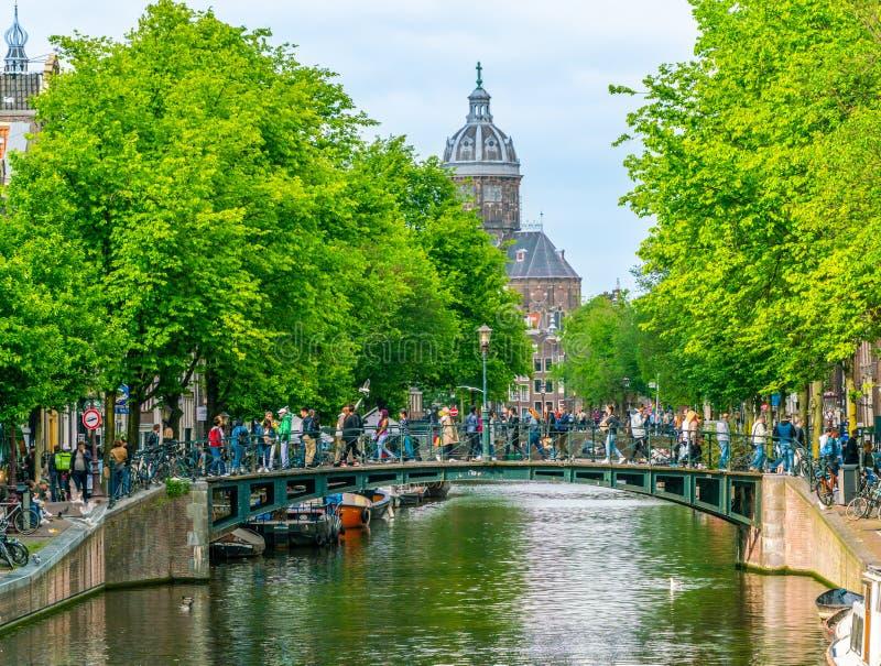 Het Oudezijdsvoorburgwal-kanaal met in de toeristen die als achtergrond door brug en oude Chruch Oude Kerk van Amsterdam kruisen stock afbeelding
