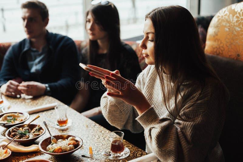Het Oungmeisje neemt beelden van voedsel Een jong bedrijf van mensen rookt een waterpijp en communiceert in een oosters restauran stock foto