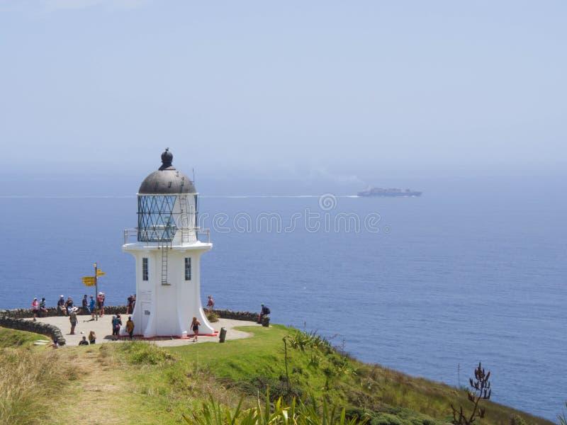 Het overgaan van schip bij de Vuurtoren van Kaapreinga, het noordenrand van Nieuw Zeeland stock afbeelding