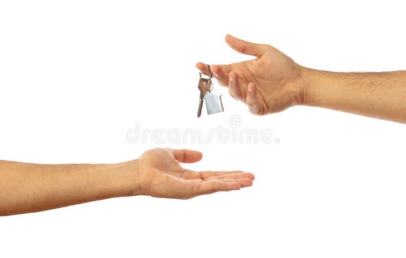 Het overhandigen van de huissleutel Handen op witte achtergrond, het knippen weg worden geïsoleerd die stock afbeeldingen