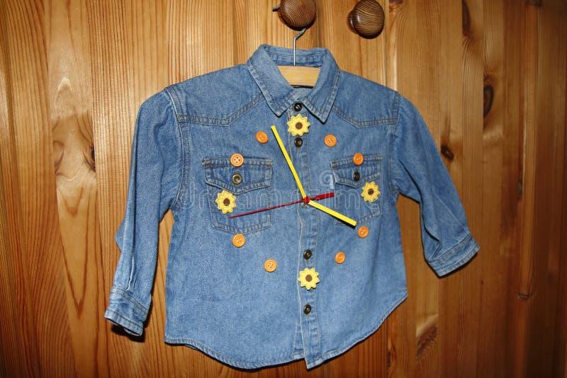 Het overhemd van kinderenjeans in ambachten in een klok zet om royalty-vrije stock afbeelding