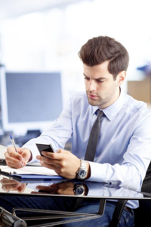 Het overseinen van de zakenmantekst op mobiel in bureau stock afbeeldingen