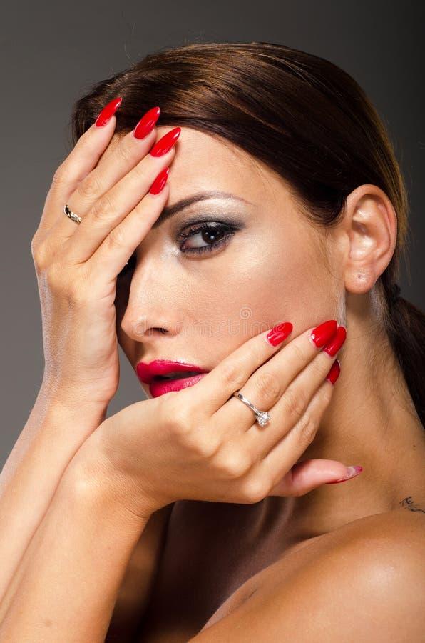 Het overweldigen brunette met handen op haar gezicht stock fotografie
