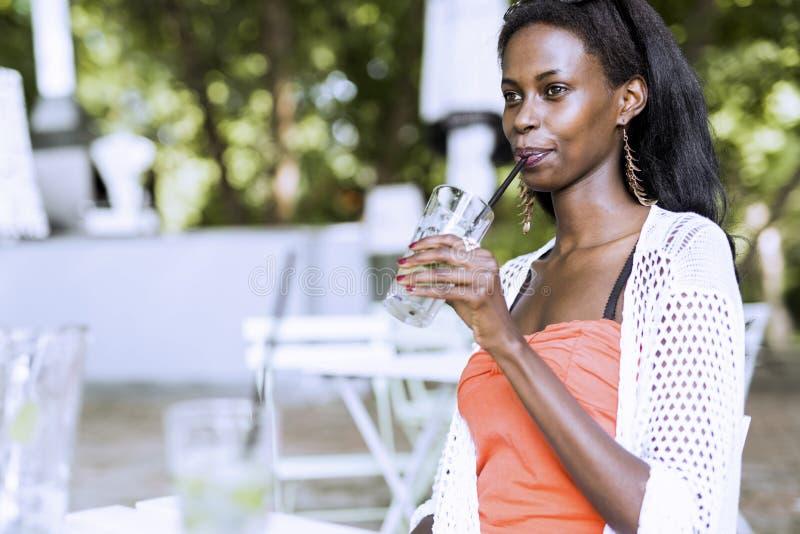 Het overweldigen van Afrikaanse vrouw die een drank op een de zomerdag drinken royalty-vrije stock afbeeldingen