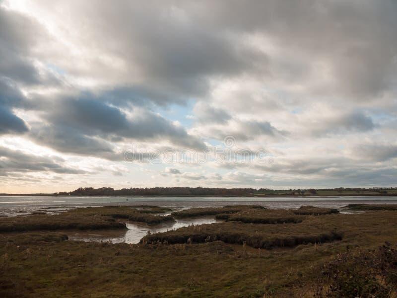 Het overweldigen van dramatische wolkenhemel over de rivieroceaan van het estuariummeer coastl stock foto