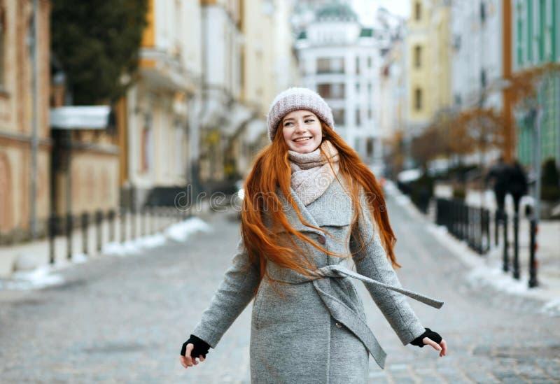 Het overweldigen van glimlachende roodharigevrouw die modieuze de winteruitrusting dragen wal stock foto