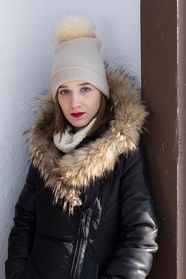 Het overweldigen van jonge vrouw in bont-in orde gemaakte laag en hoed die tegen een witte roughcast muur leunen royalty-vrije stock foto