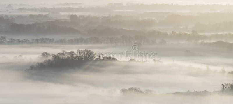 Het overweldigen van mistig Engels landelijk landschap bij zonsopgang in de Winter met stock afbeelding