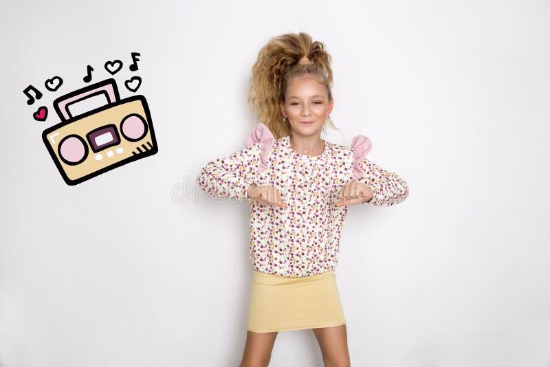 Het overweldigen van mooi meisje met lang blond haar die zich op een witte achtergrond bevinden en aan muziek dansen stock foto's